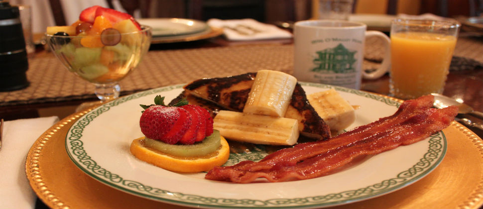 breakfast plate with bananas foster french toast, bacon, a fruit cup and orange juice