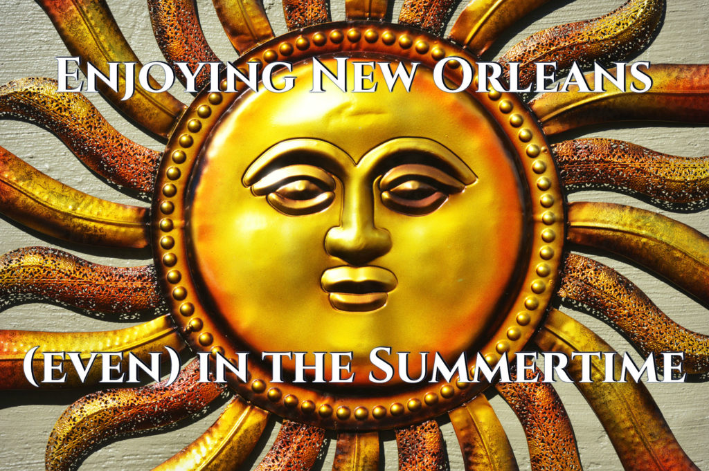 "Large Golden Smiling Sun Icon with ""Enjoying New Orleans (Even) In the Summertime"" in large white text"